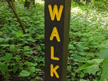 Walk sign, yellow letters on brown wood post stock images