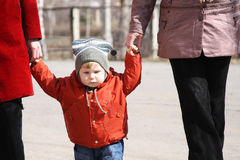 Walk in the spring. The small beautiful boy studies to go by means of adults Stock Photo
