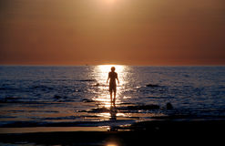 Walk sun warm0625b. Boy silhouette walking in the reflection of sunlight. having fun in the sparkling reflection on the blue water, hazy sky, warm colors royalty free stock image