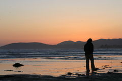A walk at sunset. One person alone on beach iwalking at evening Royalty Free Stock Photo