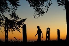 Silhouette of man walking by farm at sunset Stock Images