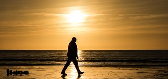 Walk on a sunset. The silhouette of a human figure walking on the beach at Ogmore-by-sea Stock Photos