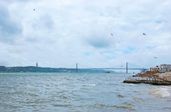 The walk by Tagus river. The view from Columns Pier on the stormy Tagus river, bridge of 25 April and the monument of Christ the King Cristo Rei on background Royalty Free Stock Photography