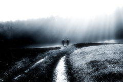 Walk throw autumn fog. Two women are going on a field throw a foggy landscape with big actinism royalty free stock photos