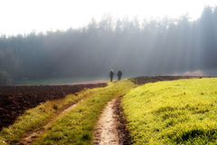 Walk throw autumn fog. Two women are going on a field throw a foggy landscape with big actinism Royalty Free Stock Photography