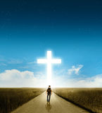 Walk to the cross. A man walking towards a large glowing Christian cross royalty free stock photos