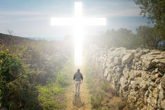 Walk to the Cross. Man walking to a Christian Cross of light stock photography