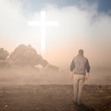 Walk to the Cross. Man walking to a Christian Cross of light royalty free stock image