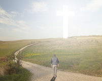 Walk to the Cross. Man walking to a Christian Cross of light royalty free stock images
