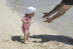 Walk to daddy. Father and young daughter at the beach for first time Royalty Free Stock Images