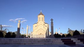Walk to the entrance to Sameba church on a background of blue sky, early evening stock footage