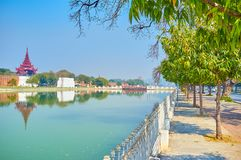 The walk to the Royal Palace in Mandalay. The pleasant walk along the moat to the entrance of Royal Palace in Mandalay with great view on the walls and oriental royalty free stock photography