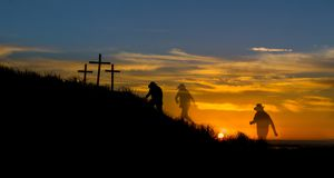 Walk to salvation. Cowboy hated man walking to three cross hill as the sunsets Stock Photos