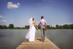 Walk together. Young happy newlyweds walking and posing on a riverside Royalty Free Stock Photos