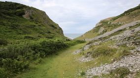 Walk valley path to Mewslade Bay The Gower peninsula south Wales UK near to Rhossili beach and Fall Bay stock video