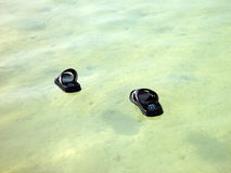 Walk on water. Two sandals floating on the water, with its shadows underneath Stock Image