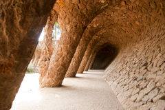 Walk way by Antoni Gaudi in park Guell. Here you can see a walkway supported by twisting rock pillars that seem to be growing out of the ground like tree trunks stock photos