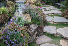 Walk way in beautiful garden with small waterfall Royalty Free Stock Images