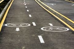 Walk way and bicycle lane signs on the asphalt road surface.  Royalty Free Stock Image