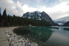 Walk way near pristine lake and snow mountain Royalty Free Stock Photography