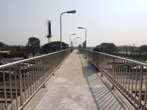 Walk way on the overpass bridge. In sunny daylight with shadow and white sky background Royalty Free Stock Photo