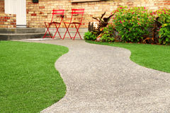 Walk way with Perfect grass landscaping with artificial grass in residential area Stock Photo