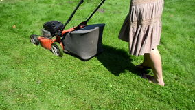 Walk woman girl skirt flip-flop shoes cut lawn grass mower yard stock footage