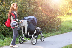 Walk women with stroller summer sunlight Royalty Free Stock Image
