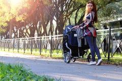 Walk women with stroller summer sunlight Royalty Free Stock Photo