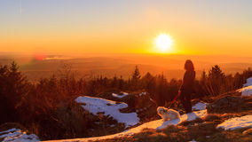 On a Walk. Young Man with his Dog on a walk against the setting winter sun in the mountains of Bavaria; Winter Sunset: Early March Winter Landscape Picture in Royalty Free Stock Photos
