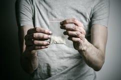 Walka przeciw lekom i narkomania tematowi: nałogowa mienia pakunek kokaina w szarej koszulce na ciemnym tle Fotografia Stock