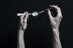 Walka przeciw lekom i narkomania tematowi: ręka nałogowa kłamstwa na zmroku stole wokoło go i są lekami, odgórny studio Obrazy Stock