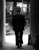Walker. Man walking with hands in pockets, through an alley way, deep in thoght Royalty Free Stock Image