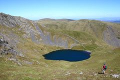 Walker Blencathra with Scales Tarn and Sharp Edge. Male walker looking at view down to Scales Tarn from slopes of Blencathra also known as Saddleback in the royalty free stock photography