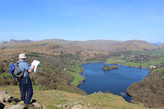 Walker with map looking to Grasmere, Lake District. A fellwalker stood on the northern slopes of Loughrigg in the English Lake District, Cumbria looking at a map Stock Images