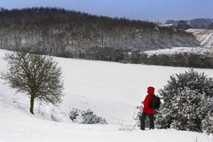 A walker on a snow covered hillside Stock Photo