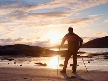 Walker watch sunny spring daybreak over sea. Hiker with backpack stand on sandy shore. Sun rays Royalty Free Stock Photos
