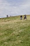 Walkers. A group of walkers heading uphill on the green field, Brecon Beacons, Wales, UK Stock Images