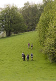Walkers. A group of walkers heading uphill on the green field in the springtime, Brecon Beacons, Wales, UK Stock Photography