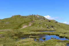 Walkers approaching mountain top and trig point Stock Photography