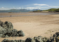 Walkers on beach at Newborough, Anglesey Wales Stock Image