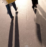 Walkers cast shadows. Walkers casting shadows on a smooth pavement Stock Photography