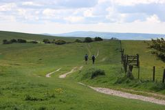 Walkers countryside england. Walkers hiking along the South Downs Way in the English countryside near Lewes, Sussex Royalty Free Stock Photography
