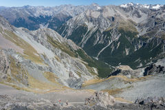 Walkers descending to alpine valley in Southern Alps Royalty Free Stock Images