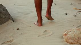 Walkers feet on a white sandy beach with rocks dry