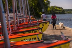 Sailboats on the shore of Lake Mendota, Madison, Wisconsin. Walkers pass by rows of sailboats on the shore of Lake Mendota in Madison, Wisconsin stock photography