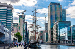 Walkers by the Stavros Niarchos ship moored at South Quay in Canary Wharf Stock Photography