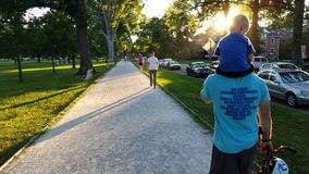 Walkers at Sunset. People enjoying the sunset on a popular walking path in Ritter Park, one of the United States top ten city parks located in Huntington, West Royalty Free Stock Image