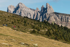 Walkers on track to Geisler Group in Dolomites Stock Photo