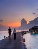 Walkibg della donna e dell'uomo di nuovo alla loro villa dell'acqua dentro Fotografia Stock Libera da Diritti
